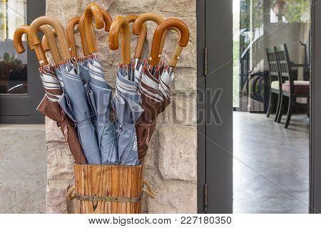 Many Folded Umbrellas Stored In Wood Container In Home