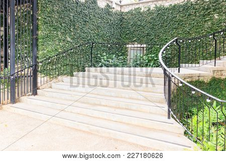 Landscape In The Park Garden.stone Staircase With Iron Railing And Surrounding Green Grass , Flowers