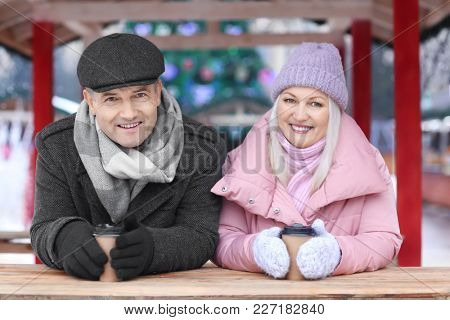 Portrait of happy mature couple drinking coffee outdoors on winter day