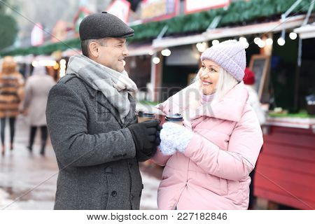 Happy mature couple drinking coffee outdoors in winter