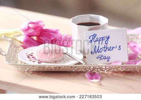 Tasty dessert and cup of coffee with card on tray. Mother's day breakfast