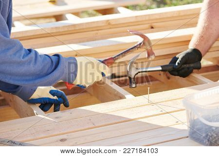 Wod carpentry. Worker hammering nail