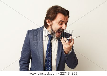 Angry Businessman Talking On Phone, Shouting At It. Job Problems Concept, Copy Space, White Studio B