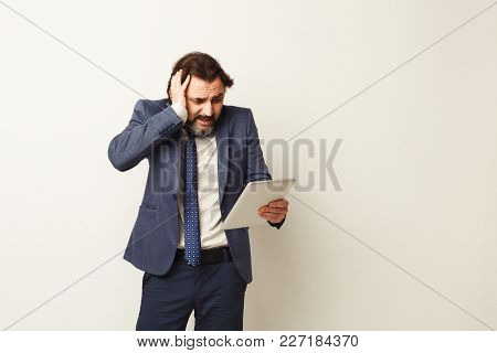 Shocked Stressed Businessman Looking At Digital Tablet Screen, Touching His Head, White Studio Backg