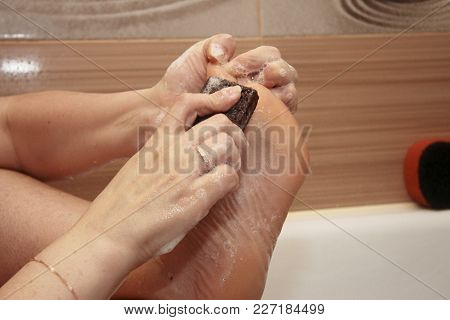 Woman Cleaning Her Feets By Pumice In Bath