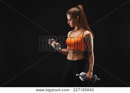 Athletic Young Woman With Dumbbells On A Black Background. Studio Shot, Low Key, Copy Space. Bodybui