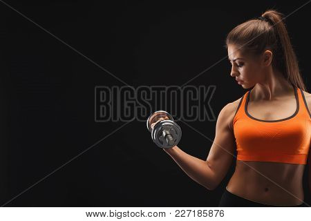 Athletic Young Woman With Dumbbell On A Black Background. Studio Shot, Low Key, Copy Space. Bodybuil