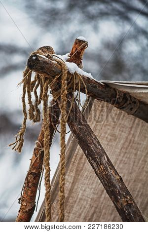 Corner Of A Roof Of Hand Made Tent Constructed Of Sticks, Rope And Linen Cloth, Covered With Snow.