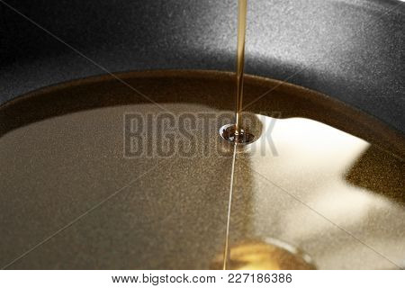Pouring cooking oil into frying pan, closeup