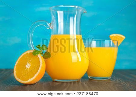 Jug and glass of fresh orange juice on wooden table