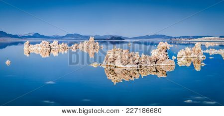 Panoramic View Of Fascinating Tufa Rock Formations Mirrored On Calm Water Surface Of Famous Mono Lak
