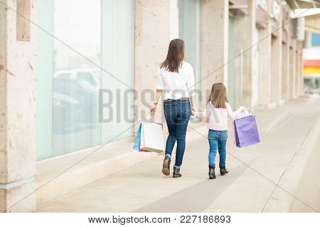 Rear View Of A Mother And Daughter Walking In Storefront Carrying Shopping Bags