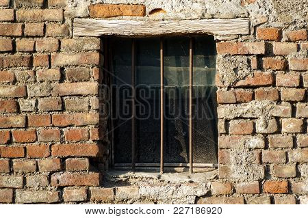 Old Brick Wall With Brick Filled Window With Grid