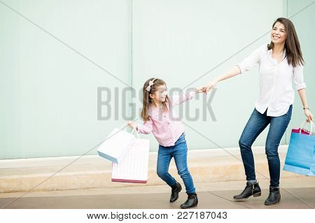 Pretty Little Hispanic Girl With Shopping Bags Pulling Mother Outside Shopping Mall