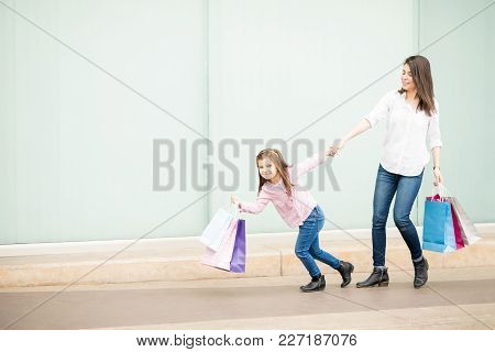 Cute Little Girl Carrying Shopping Bags Pulling Mother Outside Shopping Mall