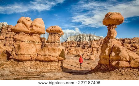 Panoramic View Of Male Person Hiking Amidst Stunning Hoodoos Sandstone Formations In Famous Goblin V