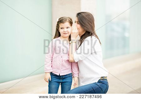 Young Latin Brunette Outside A Shopping Mall With Her Daughter And Telling Her A Secret