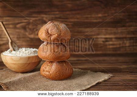 Fresh tasty buns on wooden background