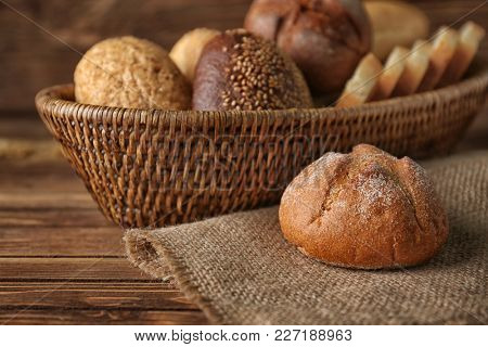 Tasty bun and wicker basket with different bread on wooden background