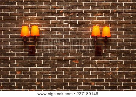 Decorative, Neat Wall Made Of Brown Ceramic Clinker Bricks And Two Wall Lamps With Orange Shades. Mo