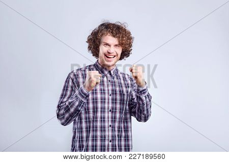Curly Young Man Surprised, Joyful Emotion On His Face On A Gray Background.