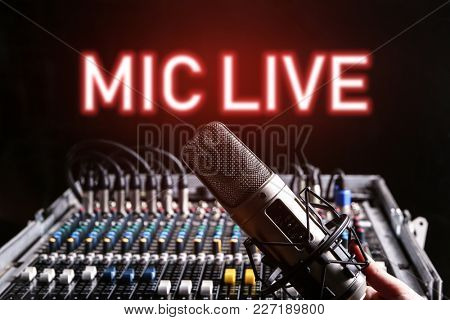 Microphone and mixer for live radio broadcast on black background