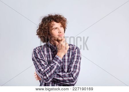 A Young Curly-haired Man With A Thoughtful Emotion Thinks Looking At The Gray Background.