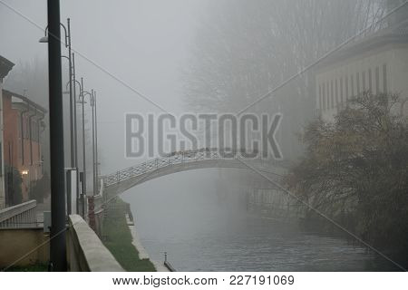 Old Arch Stone Bridge In Foggy Weather, Haze Winter In Italy