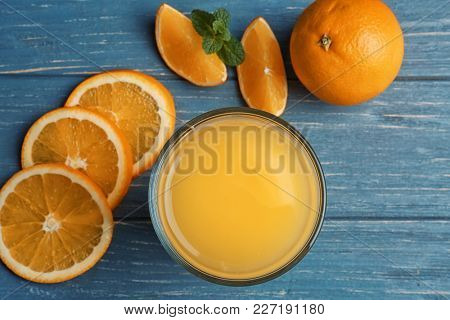 Beautiful composition with fresh orange juice and fruit on wooden table, top view