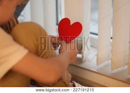 Little boy with red paper heart sitting near window. Autism concept