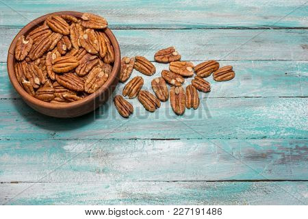 Tasty Pecan  In Wooden Bowl On The Old Background.