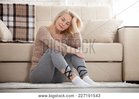 Depression. Middle Aged Barefoot Woman Sitting At The Floor Embracing Her Knees, Near Sofa At Home,
