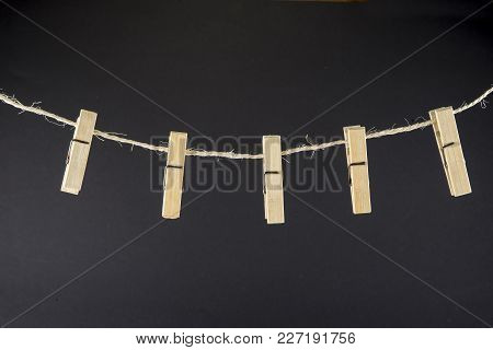 Clothes Pin On The Rope On The Black Background