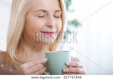 Portrait Of Happy Middle Aged Woman With Mug In Hands