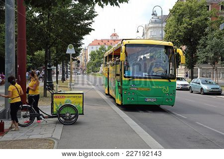Vienna, Austria - July 12, 2015: Two Promoters With Cargo Bicycle And Sightseeing Tourist Bus In Vie
