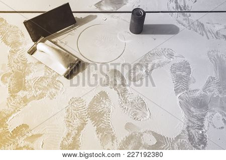 Tools With Sandpaper  And  Footprints From Workers Shoes On The Dust From Construction In Room  Is U
