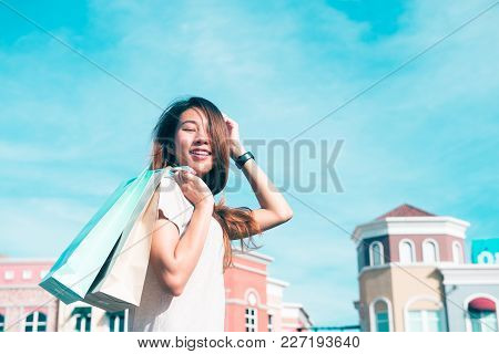 Close Up Of A Young Asian Woman Shopping An Outdoor Flea Market With A Background Of Pastel Buliding
