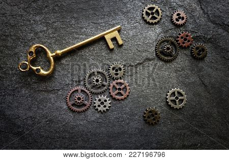 Gold Key And Assorted Metal Gears On Textured Background