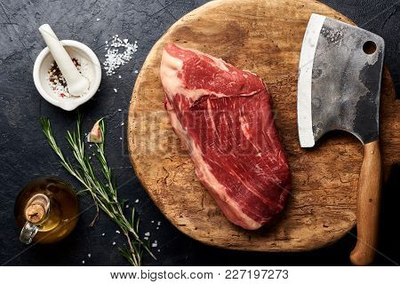 Raw Fresh Marbled Meat Black Angus Steak And Meat Cleaver On Wooden Board. Meat On Black Background