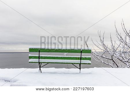 Beautiful Winter Day At Odderoya In Kristiansand, Norway. Green Bench Covered In Snow. Best Bank Of