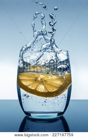 A Slice Of Lemon Falls Into A Glass Of Water