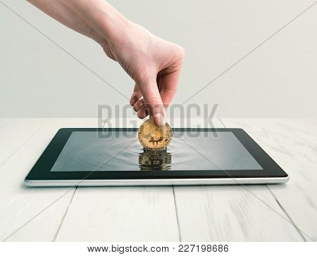 Woman Takes Out Bitcoin From A Tablet Screen