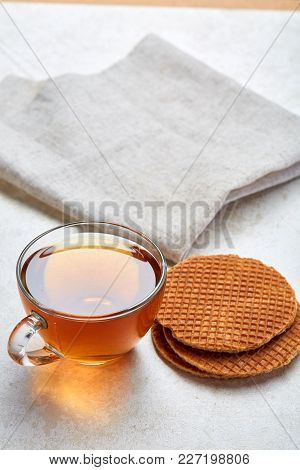 Some Black Or Herbal Tea In Transparent Cup With Tasty Waffles On Light Grey Burlap Cotton Napkin Is
