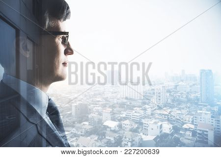 Side View Of Young European Businessman On Abstract City Background With Copy Space. Double Exposure