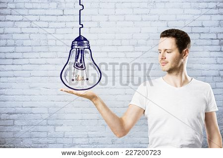 Man Holding Creative Lamp Sketch On Brick Wall Background. Leadership, Idea And Plan Concept