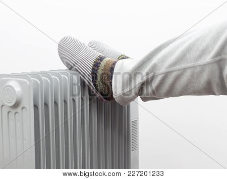 Winter Concept. Unknown Man Placed His Feet On A Heater.