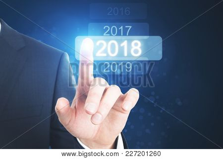 Businessman Pointing At Glowing Digital 2018 Touchscreen. Future And Innovation Wallpaper