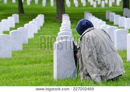 A woman prays at Arlington National Cemetery  - Washington DC United States