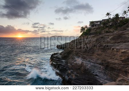 Spitting Caves In Oahu, Hawaii At Sunset With Palm Trees And Waves Crashing Against Rocks