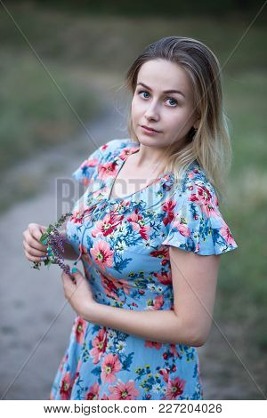Young Beautiful Woman In Flower Vintage Dress Holding Flowers In Her Hands On The Background Of Gree